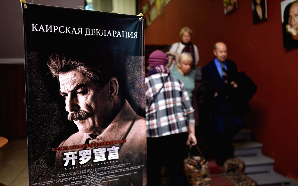 """People walk past the poster of the movie """"Cairo Declaration"""" in Movie Home, Moscow, Russia, on Dec. 3, 2015. Chinese film """"Cairo Declaration"""" is ..."""