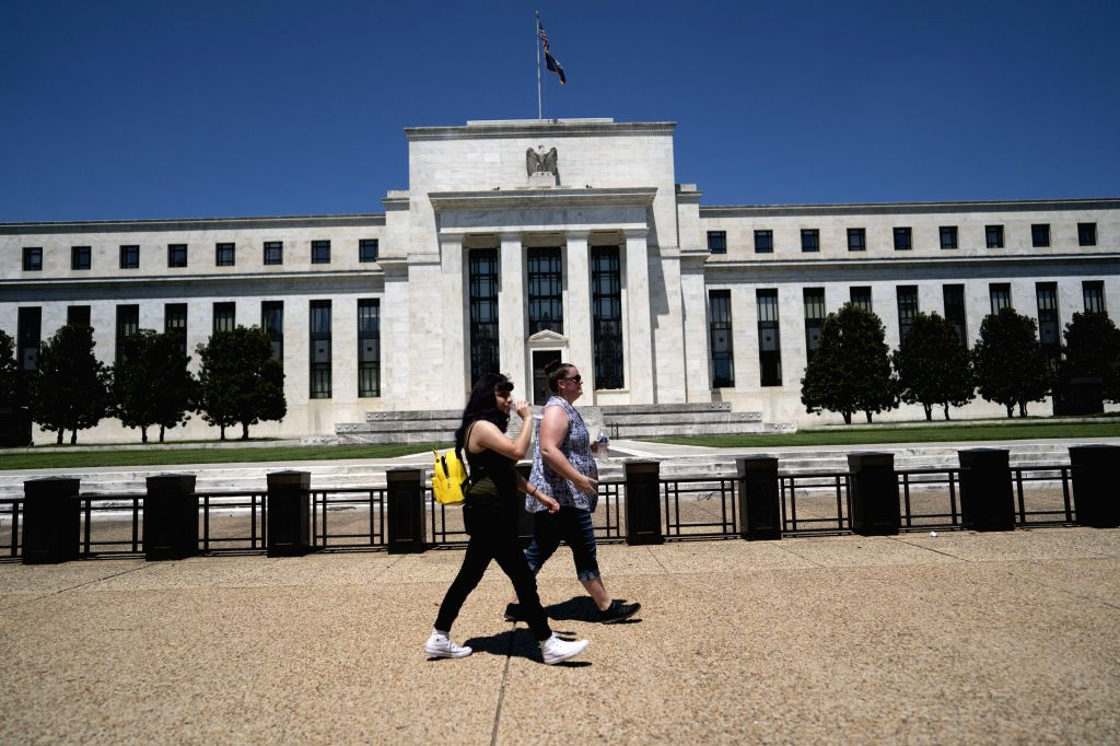 People walk past the U.S. Federal Reserve building in Washington, D.C., the United States, July 29, 2020. The U.S. Federal Reserve on Wednesday kept its ...