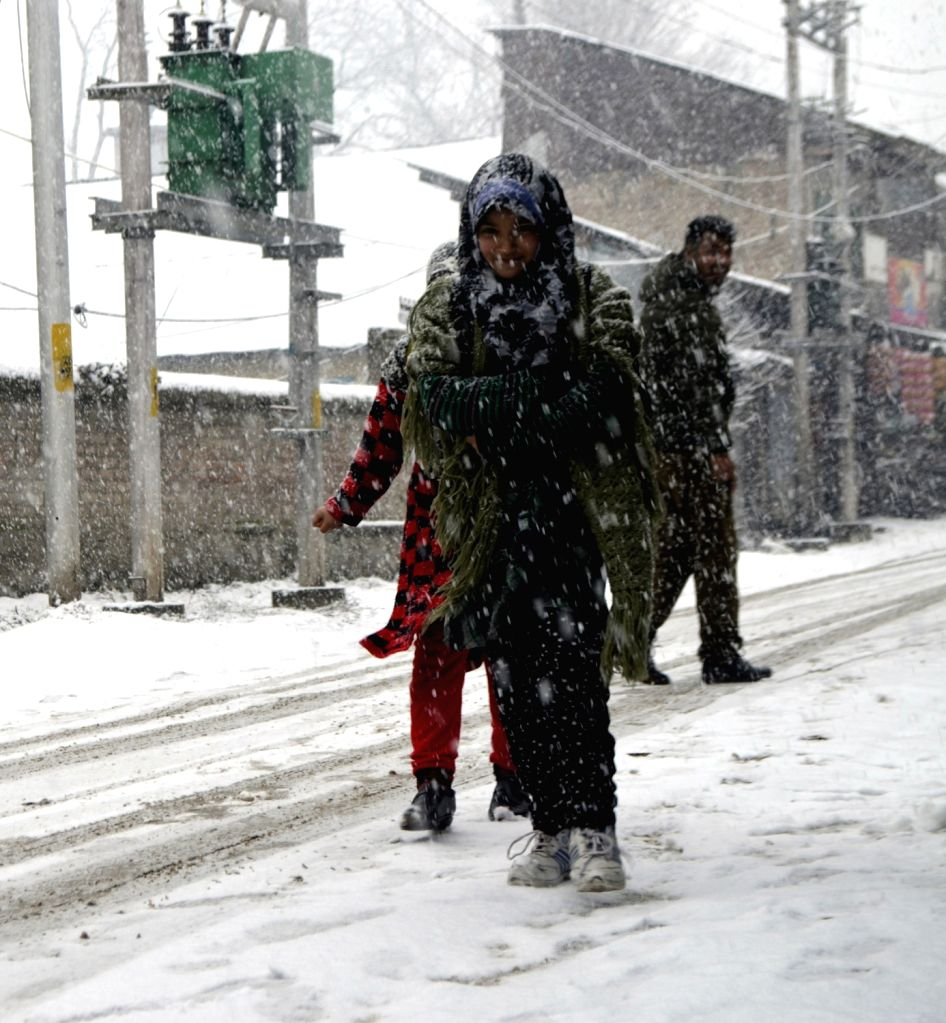 People walk through a snow covered street during fresh snowfall in Jammu and Kashmir's Baramulla, on Jan 12, 2019.