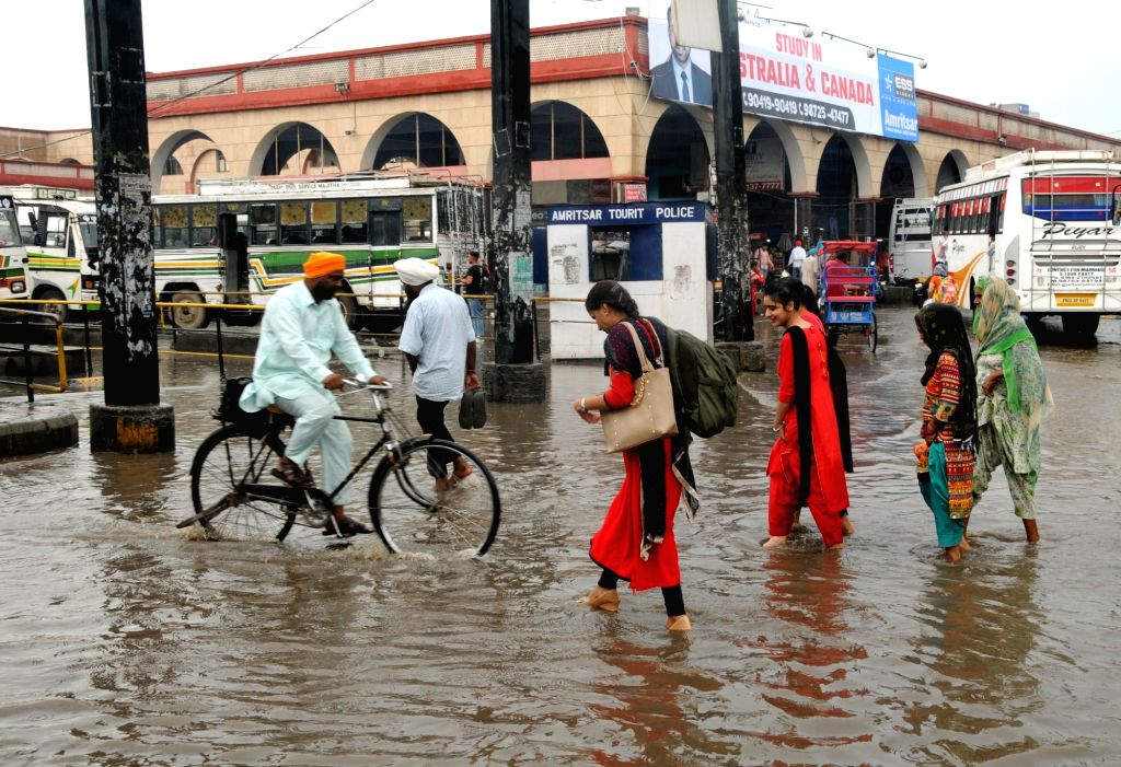 People walk through a water-logged street after rains, in Amritsar on July 25, 2019.