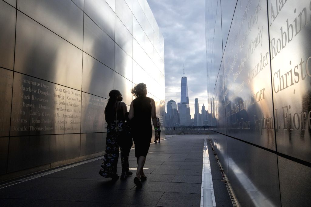 People walk through the Empty Sky memorial at Liberty State Park in Jersey City of New Jersey, the United States, on Sept. 11, 2020. People on Friday ...