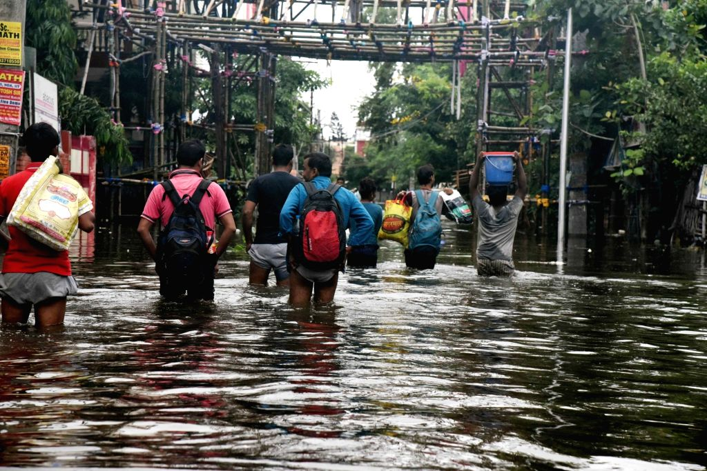 People walk through the flooded streets of flood affected Patna, on Sep 30, 2019.