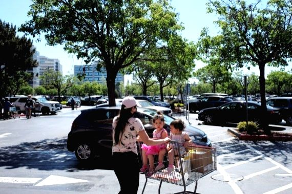 People walk to the parking lot after shopping at a supermarket in San Francisco Bay Area, California, the United States, May 4, 2021.