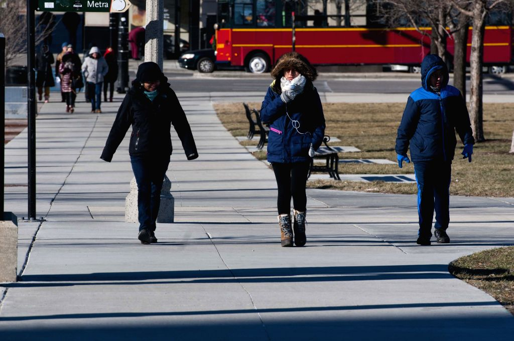 People walked on the streets with hats and gloves in Chicago, the United States on Jan. 18, 2016. It is the coldest morning of this winter season so far with ...