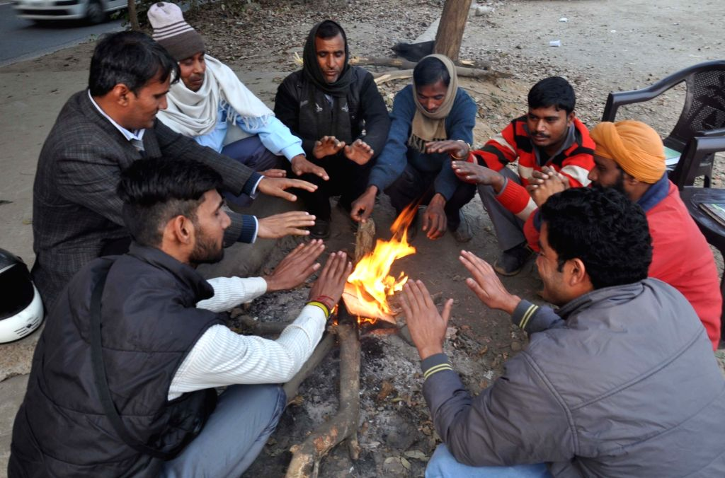 People warm themselves around a fire in Gurgaon, on Jan 20, 2016.
