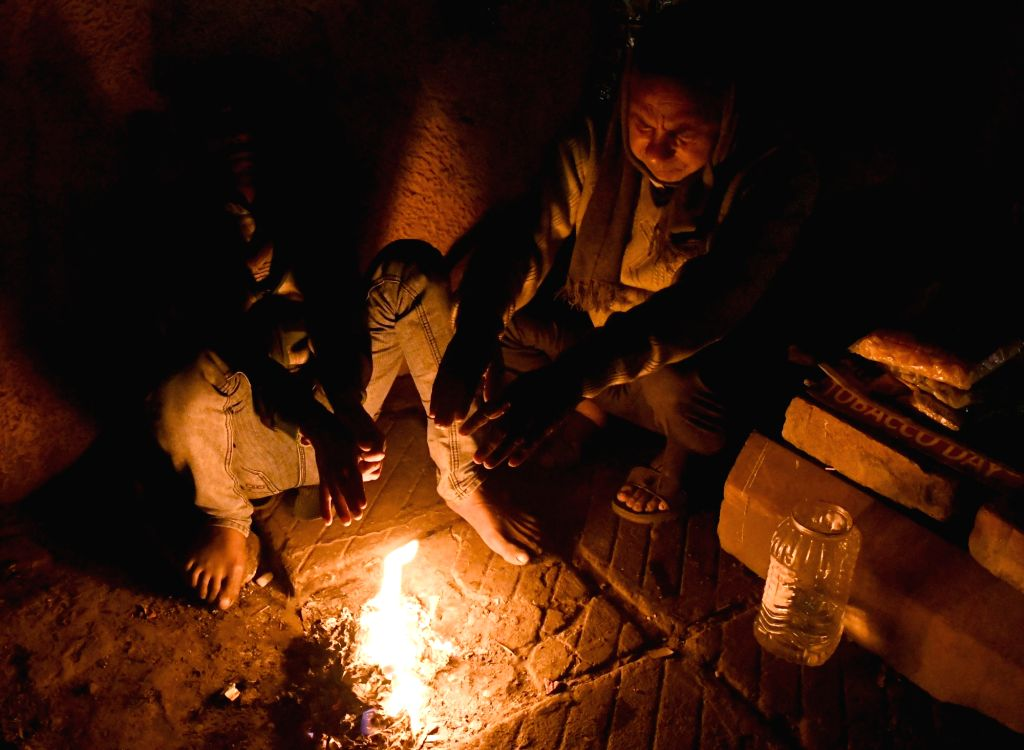 People warm themselves around a fire in New Delhi on Jan 14, 2017. The national capital continues to be in the grip of a cold wave as on Saturday it recorded the lowest temperature of the ...