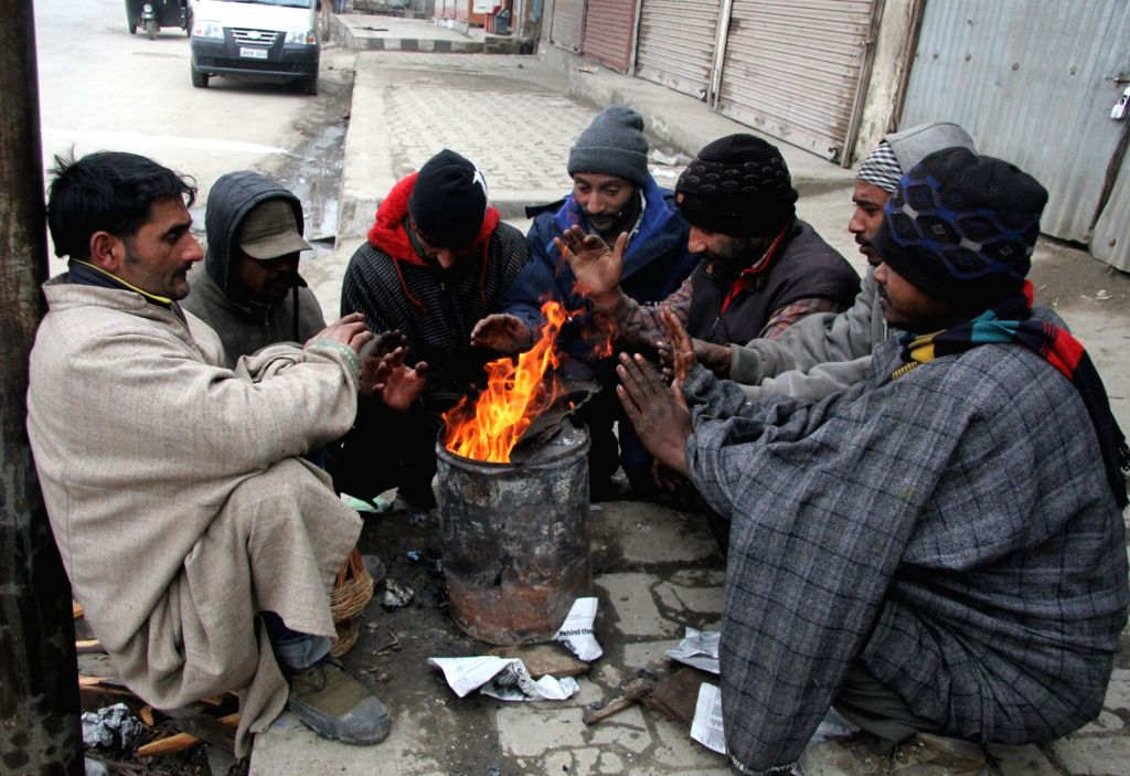 People warm themselves around a fire in Srinagar on Jan 14, 2017.