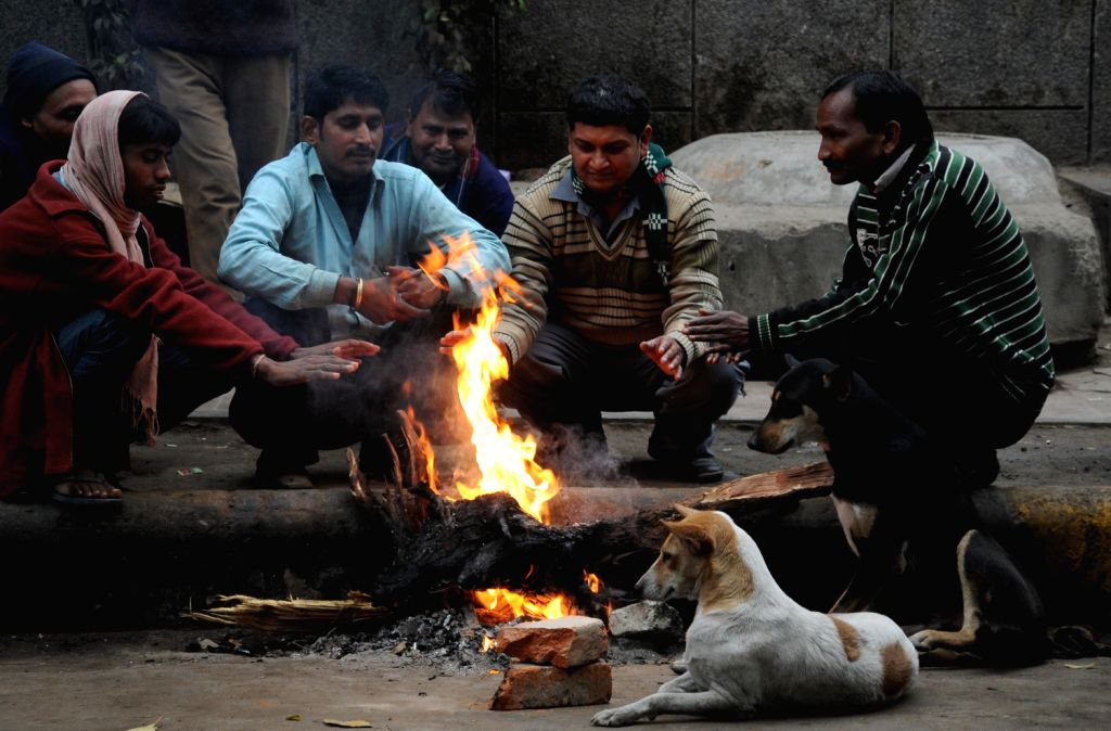 People warm themselves around a fire lit on the roadside in New Delhi on Dec.22, 2013.