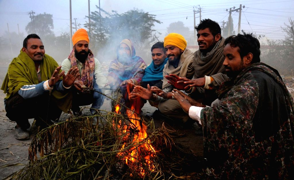 People warm themselves around a fire on a cold winter morning  in Amritsar, on Jan 19, 2016.