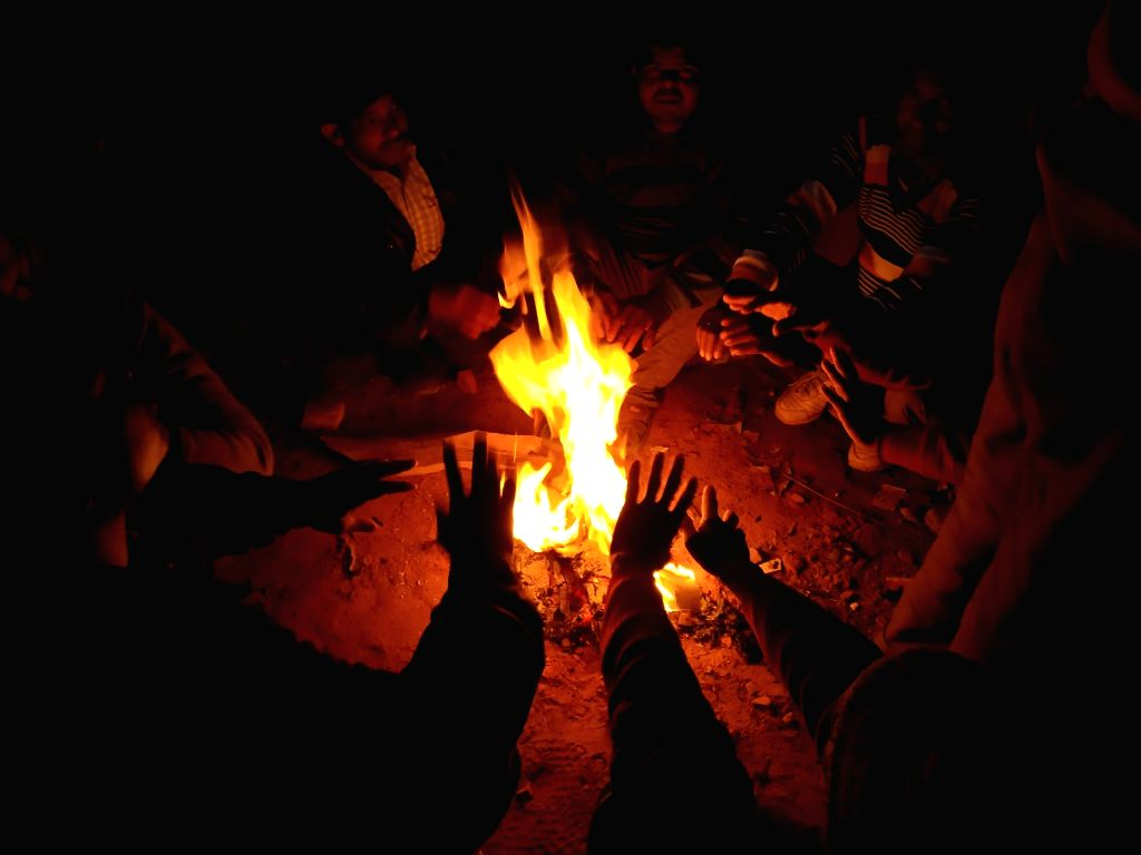 People warm themselves around a fire on a winter evening in New Delhi.