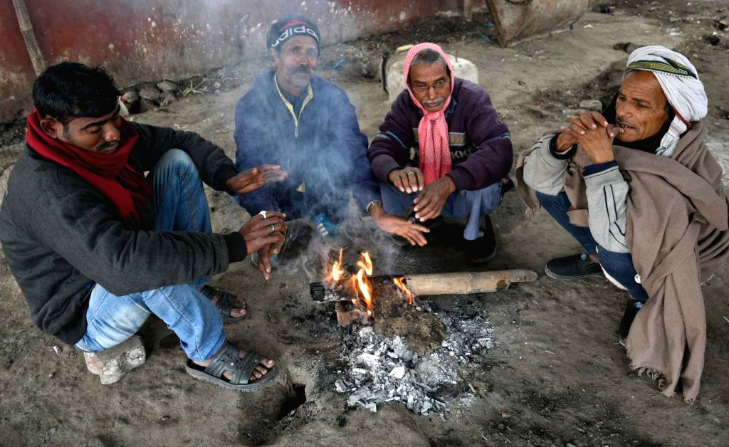 People warm themselves around a fire to beat the cold in Patna on Jan 16, 2018.