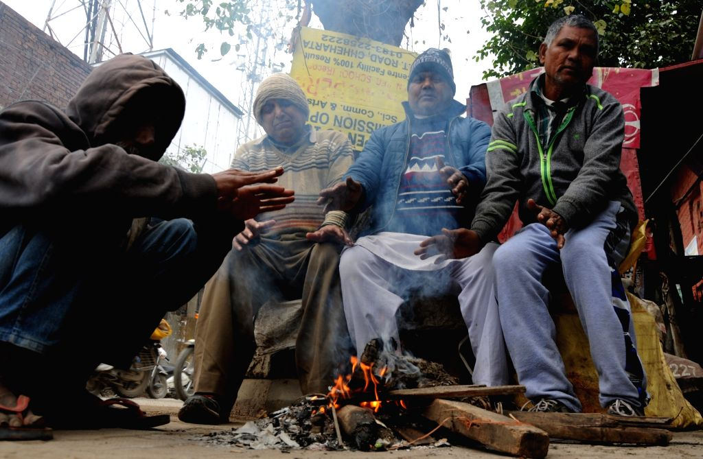 People warm themselves around the fire on a chilly winter morning, in Amritsar on Dec 17, 2019.