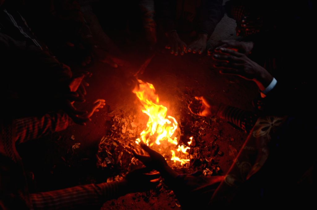 People warm themselves as winter approaches, in New Delhi on Dec.18, 2013.