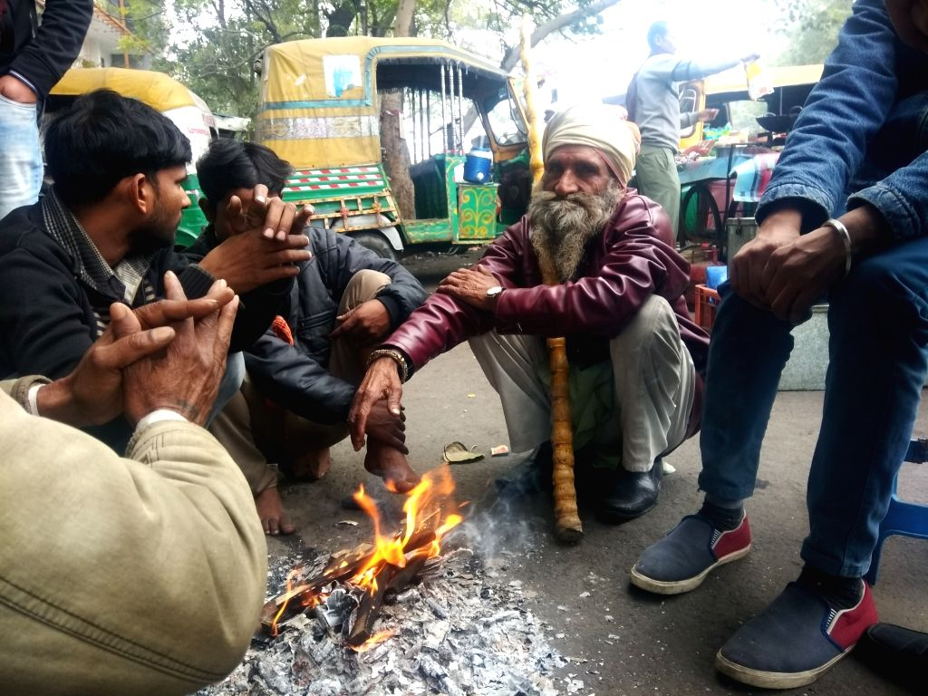 People warm themselves by a bonfire on a cold winter morning in New Delhi, on  Feb 2, 2019.