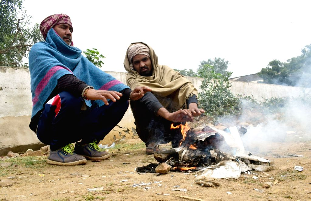 People warm themselves on a cold winter morning in Mathura on Dec 12, 2018.