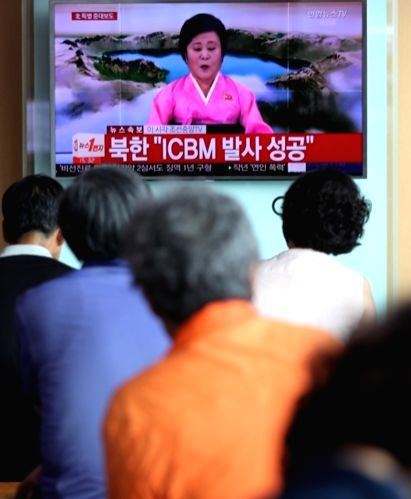 People watch a live TV report at Seoul Station on July 4, 2017, showing North Korea's special announcement that it has successfully tested an intercontinental ballistic missile.