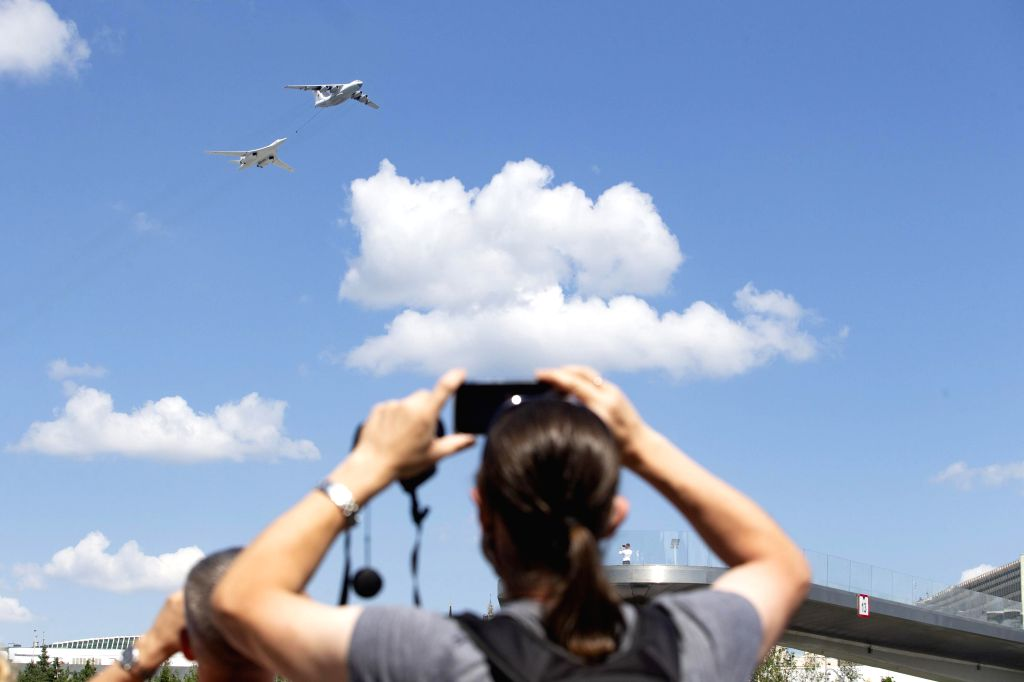 People watch an Il-78 air tanker and a Tu-160 strategic bomber flying over the Red Square during the military parade marking the 75th anniversary of the victory in ...