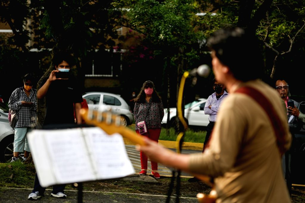 """People watch an outdoor concert themed on """"Hugs from a distance"""" amid the COVID-19 pandemic in Mexico City, Mexico, Aug. 28, 2020."""