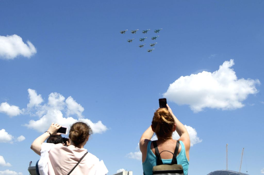 People watch Su-35S, Su-34 and Su-30SM jet fighters flying over the Red Square during the military parade marking the 75th anniversary of the victory in the Great ...