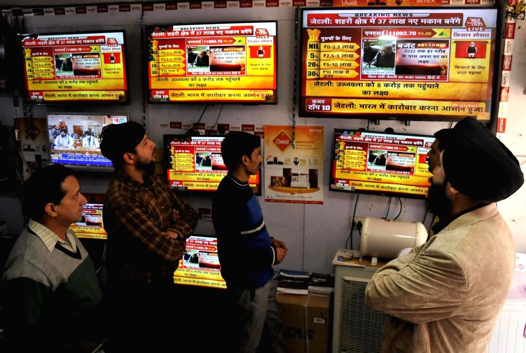 People watch the telecast of the Budget 2018-19 at a TV showroom in Amritsar 0n Feb 1, 2018.