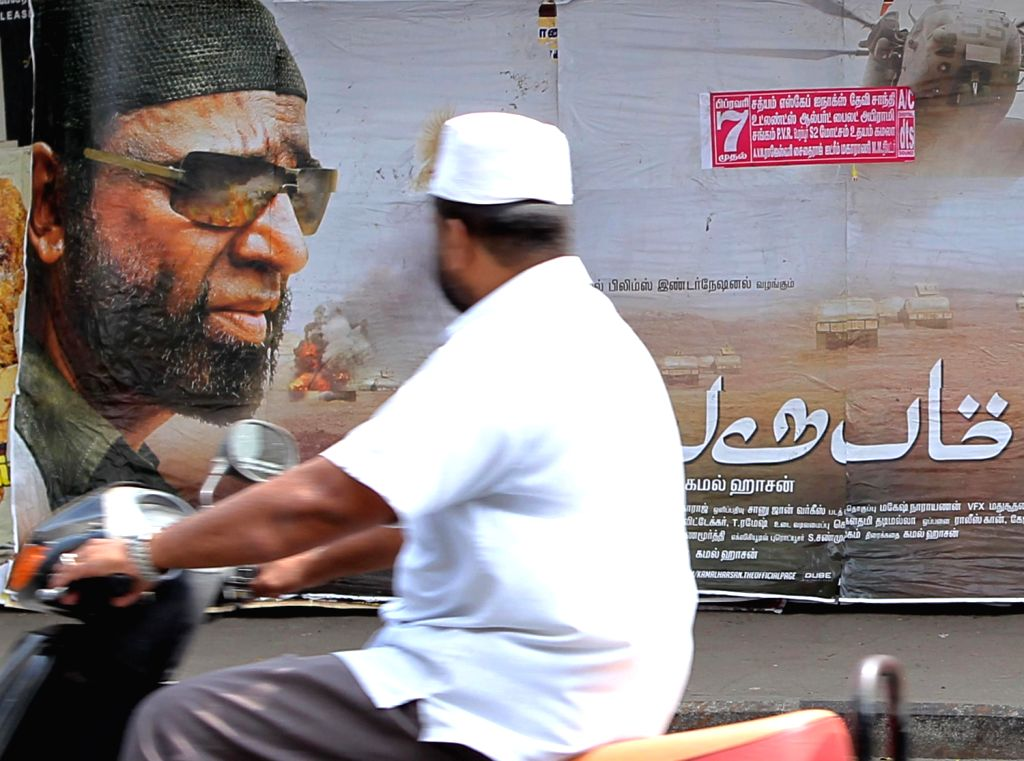 People watches poster of actor and director Kamal Haasan`s film Vishwaroopam a day before the release of the movie in Tamil Nadu, Chennai on Feb. 6.