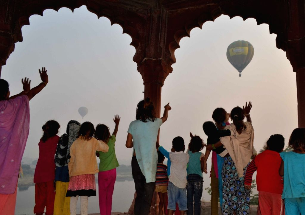 People wave at balloons on the third day of Agra balloon festival  on Nov 16, 2015.