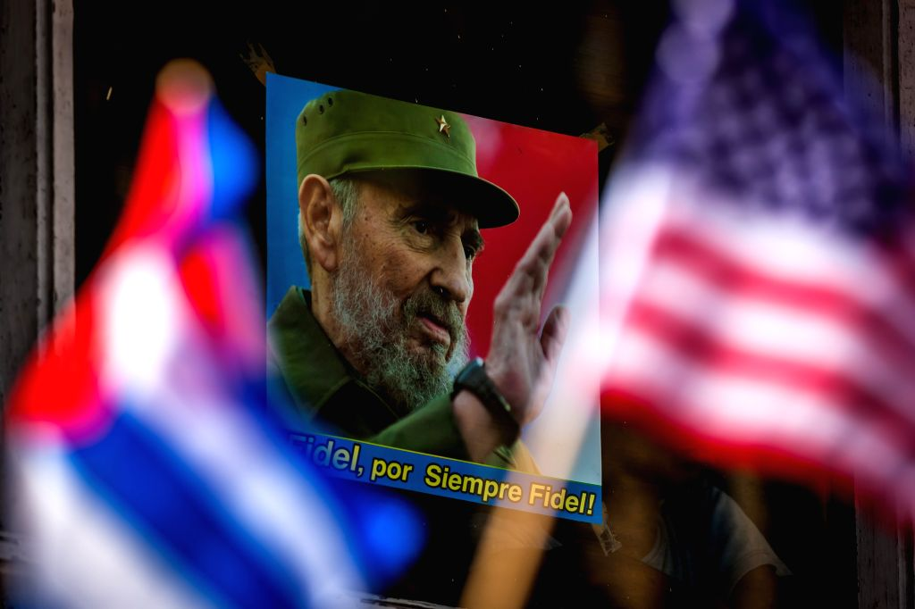 """People wave national flags of Cuba and the United States in front of a poster of Fidel Castro which says """"Fidel forever"""" during the flag-raising ceremony ..."""