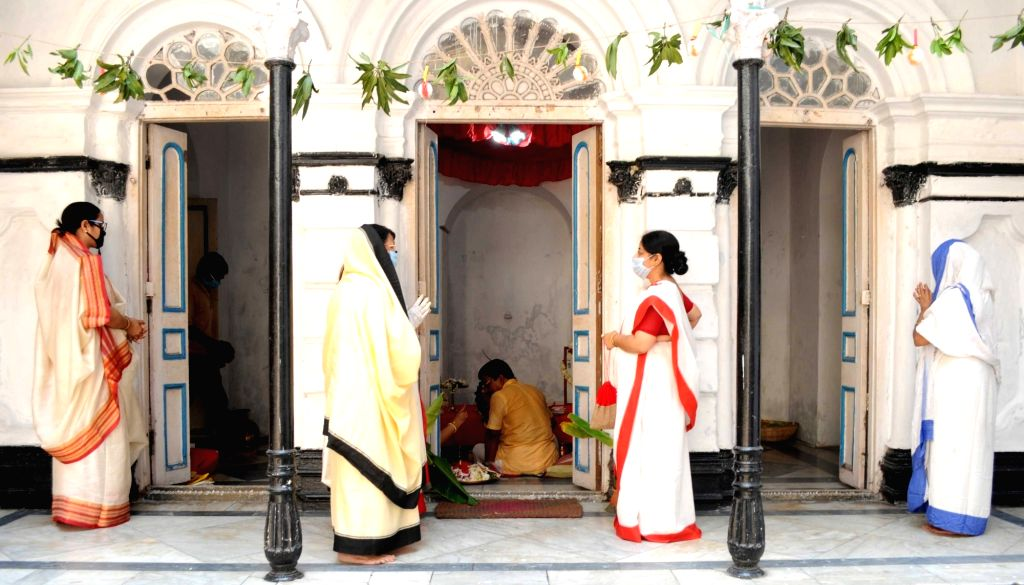 People wear mask and offer prayers to Goddess Annapurna during the 21-day nationwide lockdown imposed as a precautionary measure to contain the spread of coronavirus, in Kolkata on Apr 1, ...