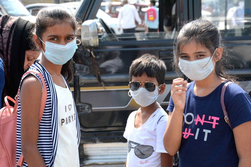 People wear masks as a precautionary measure against COVID-19 amid coronavirus pandemic, in Patna on March 20, 2020.