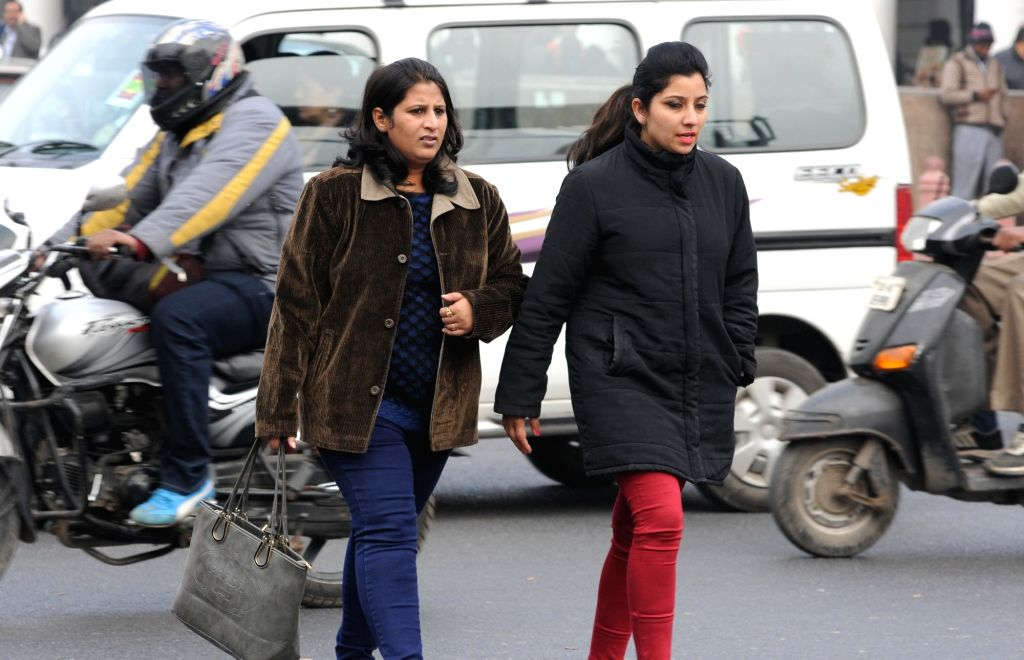 People wear warm clothes on a cold winter day in New Delhi.