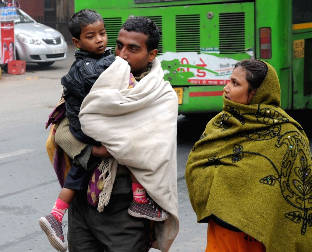 People wear warm clothes on a cold winter day in New Delhi on Jan 19, 2016.