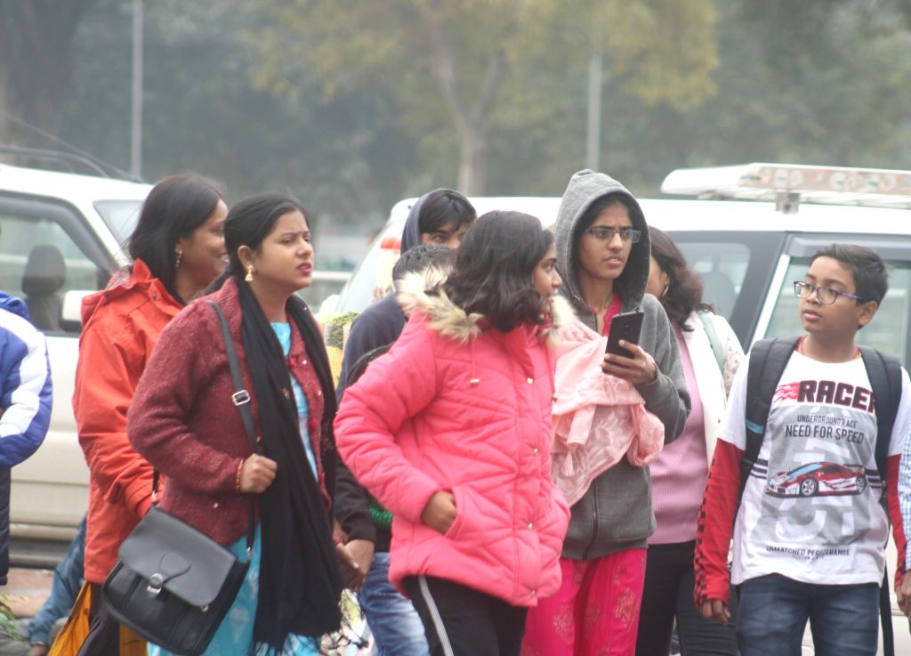 People wear woolen clothes to keep themselves warm on a chilly winter morning as temperatures dropped after rains in New Delhi on Dec 13, 2019.