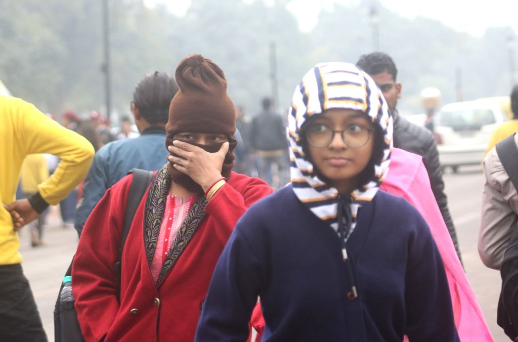 People wear woolen clothes to keep themselves warm on a chilly winter morning as temperatures came down further after rains in New Delhi on Dec 13, 2019.