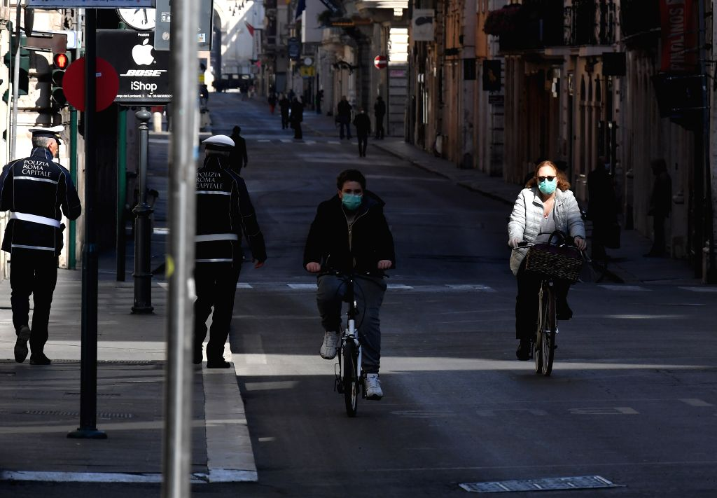 People wearing face masks are seen in Rome, Italy, on March 18, 2020. Numbers for both new deaths and new cures from Italy's COVID-19 outbreak released Wednesday are ...