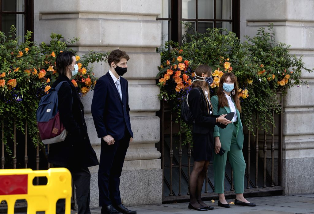 People wearing face masks are seen on a street in central London, Britain, on Sept. 12, 2020. Almost 8 million Britons will be subjected to tighter lockdown ...