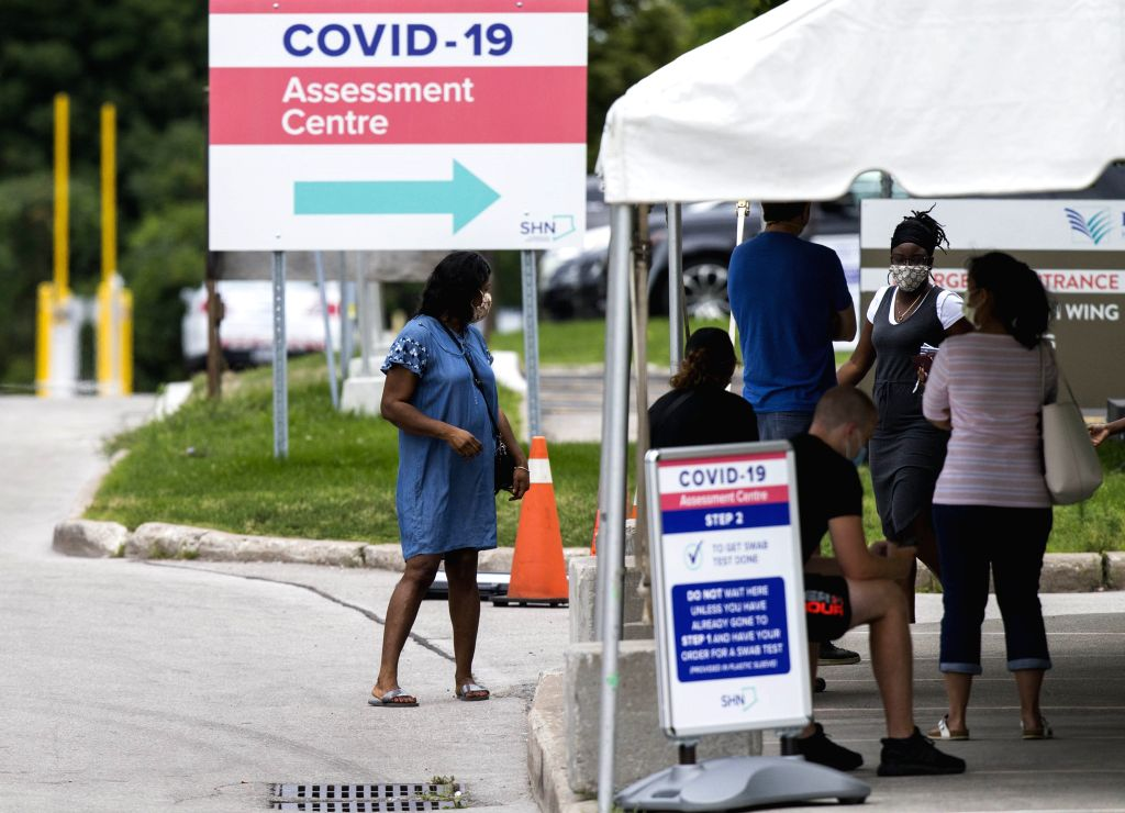 People wearing face masks line up to have COVID-19 tests at a COVID-19 assessment center in Toronto, Canada, on Aug. 11, 2020. As of Tuesday evening, Canada ...