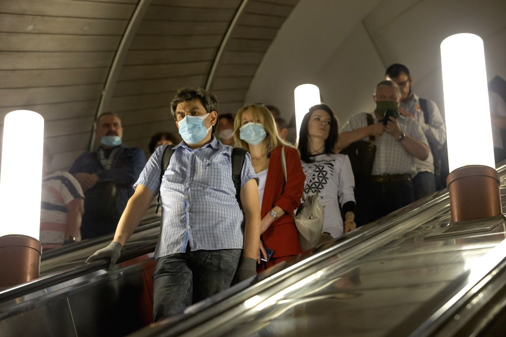 People wearing face masks ride the escalator at a subway station in Moscow, Russia, on June 23, 2020. Russia recorded 7,425 COVID-19 cases in the past 24 hours, ...