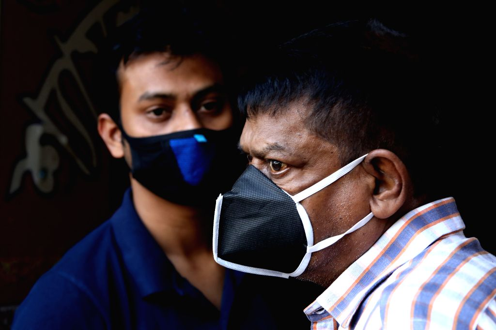 People wearing face masks wait for bus at a station in Dhaka, Bangladesh, on March 19, 2020. A total of 17 cases of COVID-19 have been confirmed in Bangladesh with ...
