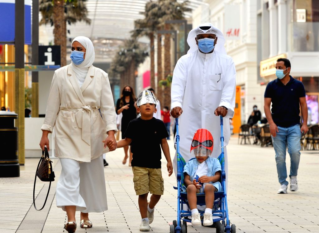 People wearing face masks walk at a shopping mall in Farwaniya Governorate, Kuwait, Oct. 17, 2020. Kuwait reported 739 new COVID-19 cases and four more deaths, ...