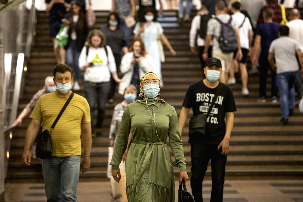 People wearing face masks walk in a subway station in Moscow, Russia, on June 23, 2020. Russia recorded 7,425 COVID-19 cases in the past 24 hours, taking its total ...