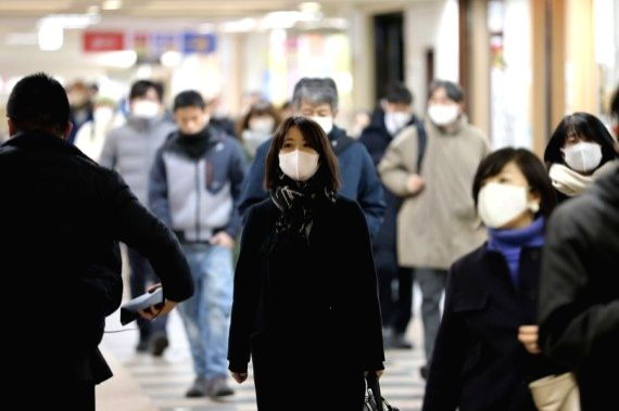People wearing face masks walk in Tokyo, Japan, Jan. 7, 2021.