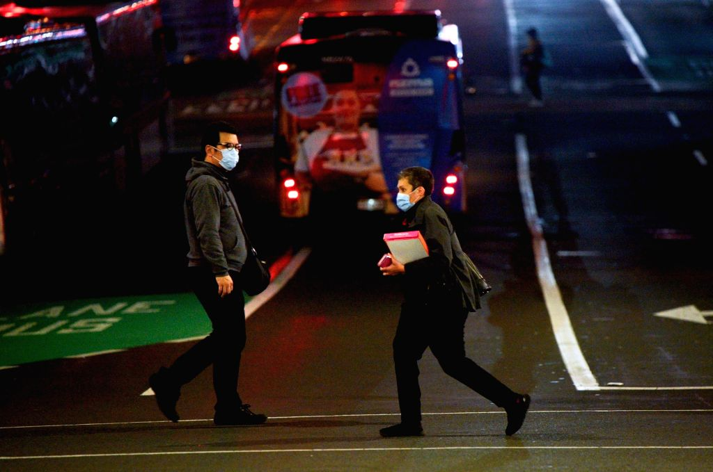 People wearing face masks walk on a street in downtown Auckland, New Zealand, Aug. 12, 2020. New Zealand's largest city Auckland resumed COVID-19 Alert Level 3 on ...