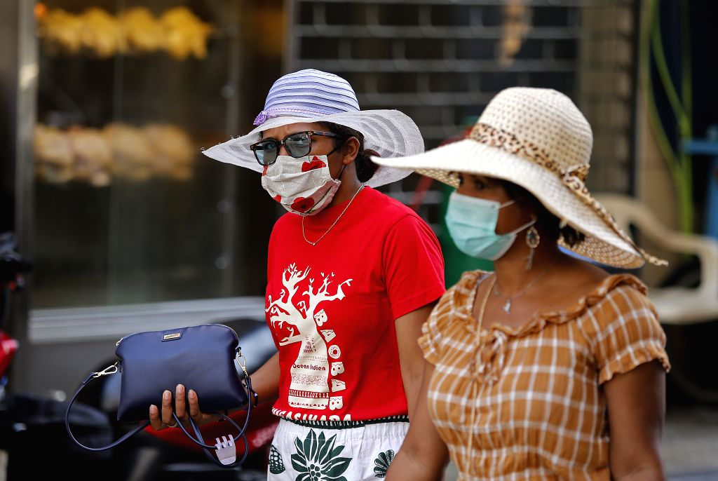 People wearing face masks walk on a street in Beirut, Lebanon, on Aug. 30, 2020. Lebanon's number of COVID-19 cases increased on Sunday by 595 to 16,870 while the ...