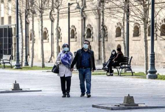 People wearing face masks walk on a street in downtown Tehran, Iran, Feb. 21, 2021.