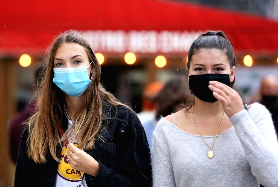 People wearing face masks walk on the Champs Elysees Avenue in Paris, France, Aug. 28, 2020.