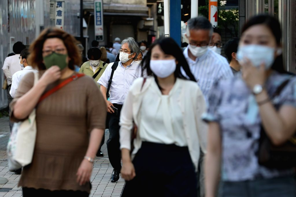 People wearing face masks walk on the street in Tokyo, Japan, on July 2, 2020. The Tokyo metropolitan government on Thursday confirmed 107 new COVID-19 infections in ...
