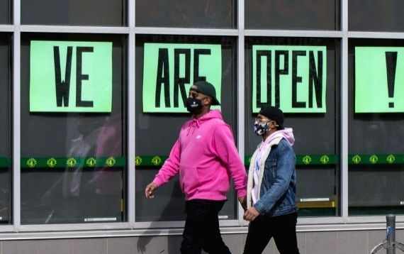 "People wearing face masks walk past a store with ""WE ARE OPEN!"" signs in Toronto, Canada, on March 8, 2021."