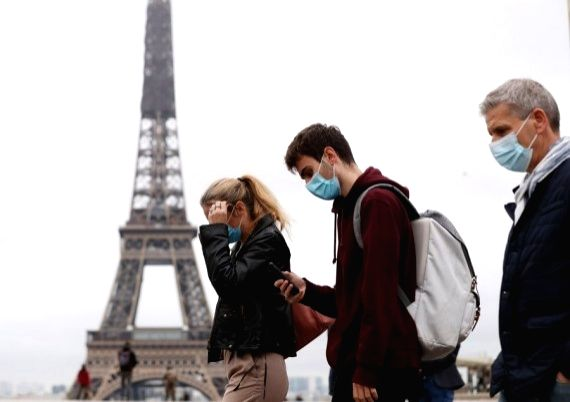 People wearing face masks walk past the Trocadero Place near the Eiffel Tower in Paris, France, Oct. 23, 2020.
