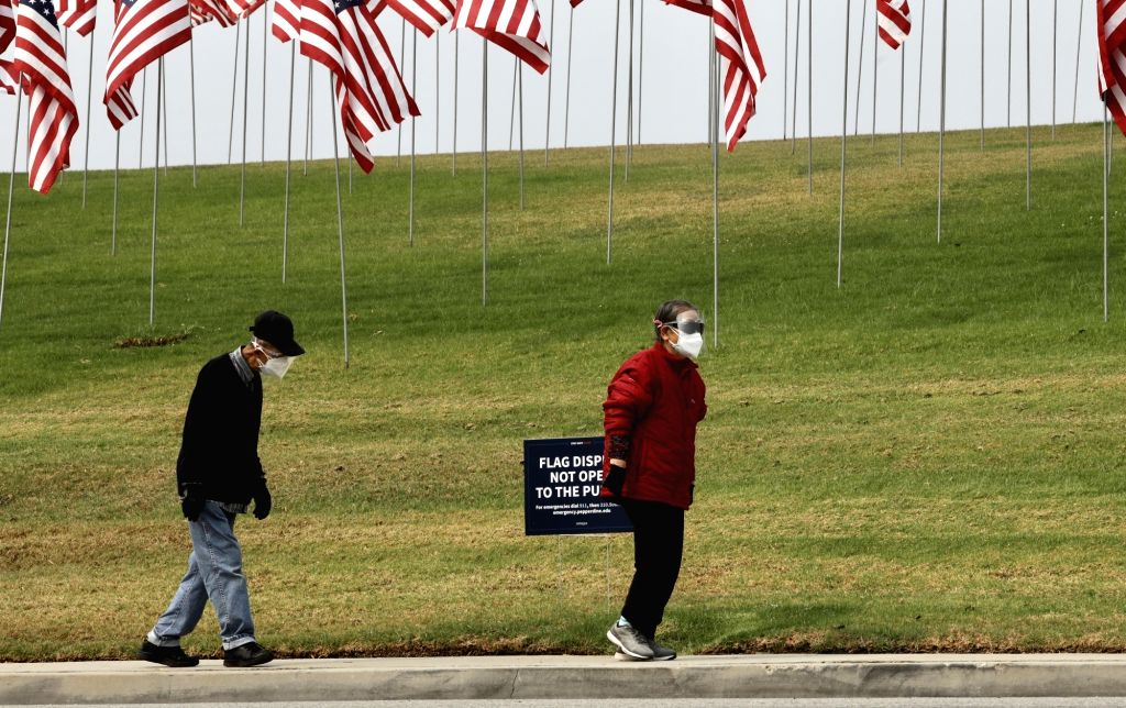 People wearing face masks walk past the Waves of Flags display at Pepperdine University in Malibu, the United States, on Sept. 11, 2020. The Waves of Flags ...