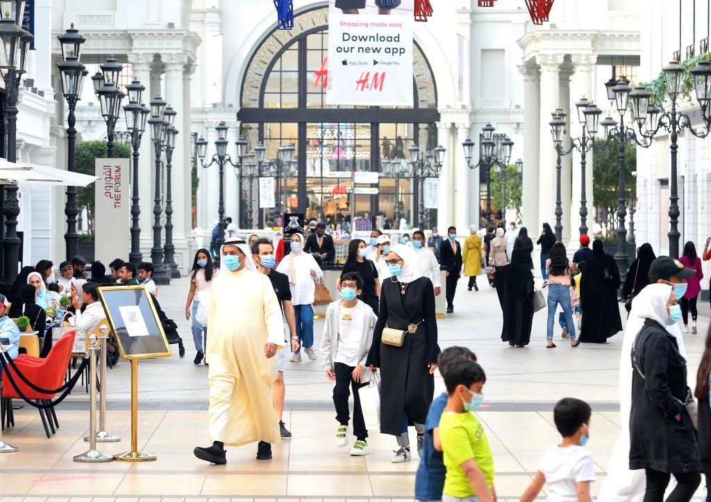 People wearing face masks work at a shopping mall in Farwaniya Governorate, Kuwait, Oct. 17, 2020. Kuwait reported 739 new COVID-19 cases and four more deaths, ...